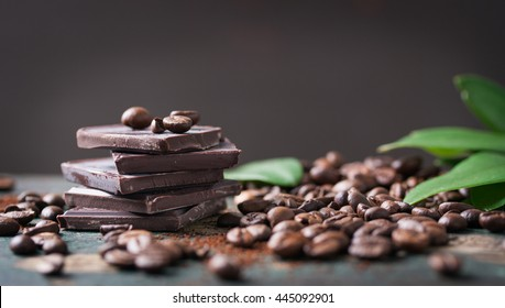 Stack of chocolate chunks with coffee beans on a wooden background, horizontal with copy space