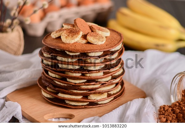 une pile de crêpes au chocolat avec de la banane sur le dessus saupoudrée de cacao