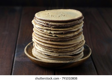 Stack of chocolate pancakes on wooden plate on dark-brown background. Traditional food for Russian holiday Maslenitsa.