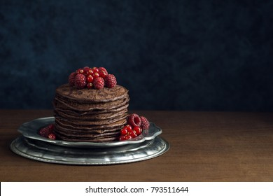 Stack of Chocolate Pancakes Topped with Fresh Raspberries and Red Currants on Metal Plate