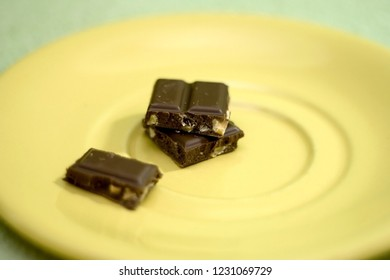 Stack of chocolate pieces, with hazelnuts. Selective focus.