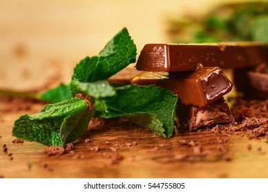 stack of chocolate pieces with a  leaf of mint on wooden background