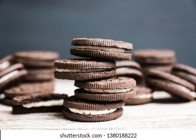 Stack of chocolate sandwich cookies on the rustic wooden background. Selective focus. Shallow depth of field.