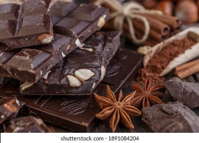 Stack of chocolate slices with mint leaf on a wooden table.Assortment of fine chocolates in white, dark, and milk chocolate. Sweet food photo concept.
