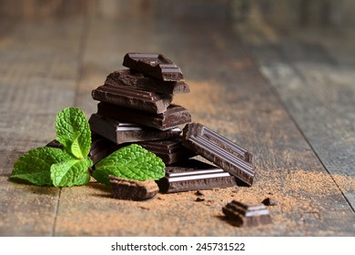 Stack of chocolate slices with mint leaf on a wooden table.