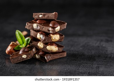 Stack of chocolate slices with mint leaf.Hazelnut and almond milk and dark chocolate pieces tower.Sweet food photo concept. The chunks of broken chocolate