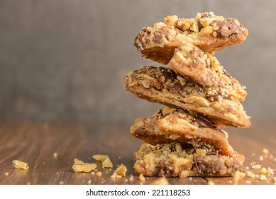 A stack of chocolate toffee nut cookies on dark wood table.