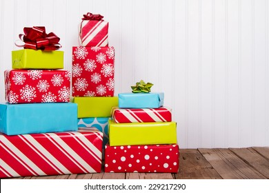 A stack of Christmas presents on rustic wood planks