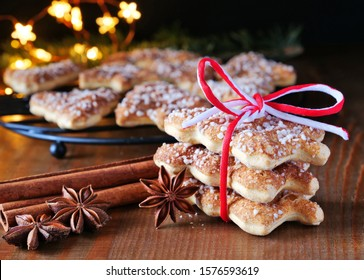 Stack of Christmas tree shaped cinnamon biscuits with spices on wooden table.