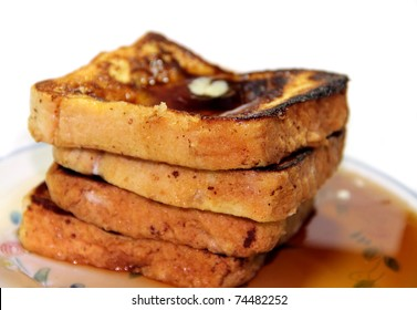 Stack of cinnamon french toast with butter and syrup with white background.