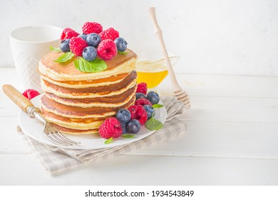 Stack of classic  American pancakes with fresh berries and maple syrup, on white table background copy space