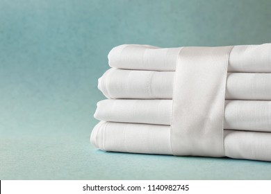 Stack of clean bed sheets on color background