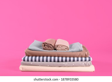 Stack of clean bed sheets on pink background. Space for text