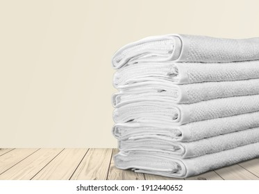 Stack of clean bed sheets and towels on table
