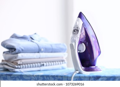 Stack of clean clothes and electric iron on board
