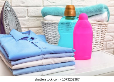 Stack of clean clothes, iron, detergents and basket with towels on table
