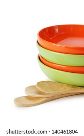 stack of clean empty plates and wooden spoons  isolated on white background