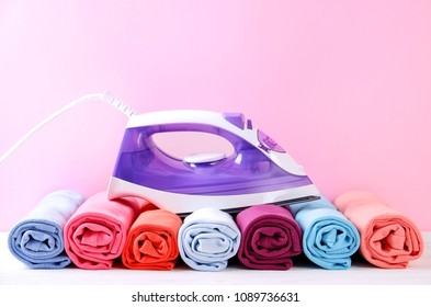 Stack of clean freshly laundered, neatly rolled clothes and electric iron on pressboard. Pile of t-shirts rolls on white wooden ironing board, pink wall background. Copy space, close up, top view.