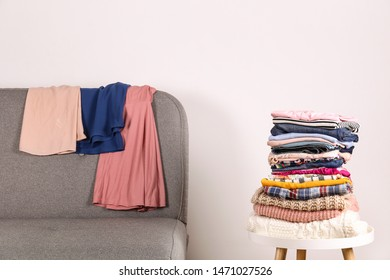 Stack of clean freshly laundered, neatly folded women's clothes on wooden table. Pile of shirts, dresses and sweaters on white board, concrete wall background. Copy space, close up, top view.