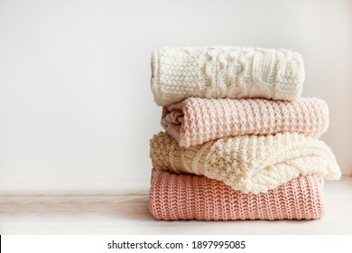 Stack of clean freshly laundered, neatly folded women's clothes on wooden table. Pile of shirts and sweaters on the table, white wall background. Copy space, close up, top view.