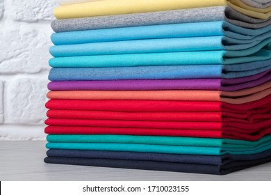 A stack of clean, neatly folded colored clothes on a light wooden table. Colors of rainbow.
