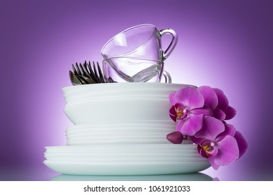 Stack of clean plates, cutlery and cups are top, near Orchid flower on lilac