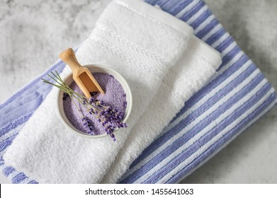 Stack of clean soft towels with a bunch of lavender and  bath salt on light gray background. Spa towels against a textured wall. Minimalism, soft focus, top view.