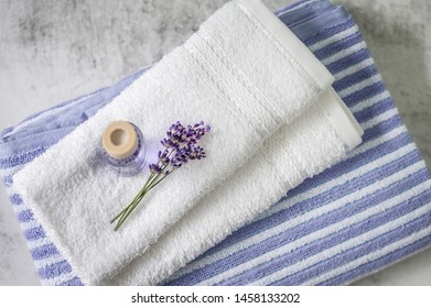 Stack of clean soft towels with a bunch of lavender and air freshener on light gray background. Spa towels against a textured wall. Minimalism, soft focus,  top view.