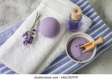 Stack of clean soft towels with a bunch of lavender, bath salt and air freshener on light gray background. Spa towels against a textured wall. Minimalism, soft focus, top view. SPA concept.