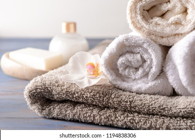 Stack of clean soft towels with flower on wooden table