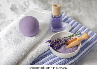 Stack of clean soft towels with lavender, air freshener and bath salt on light gray background. Spa towels against a textured wall. Minimalism, soft focus, top view. SPA concept.