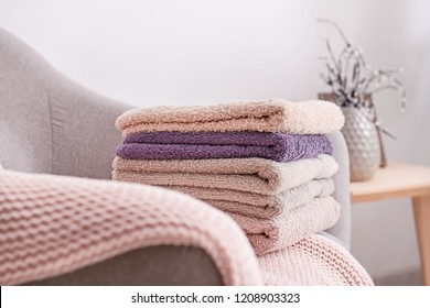 Stack of clean soft towels on sofa
