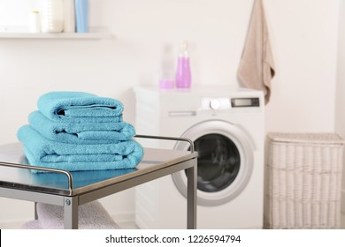 Stack of clean soft towels on table in laundry room. Space for text