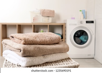 Stack of clean soft towels on basket in laundry room. Space for text