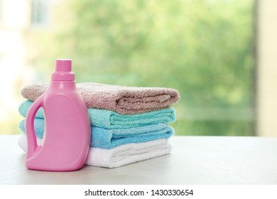Stack of clean towels with detergent on table against blurred background. Space for text
