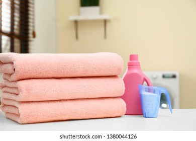 Stack of clean towels and detergents on table in laundry room