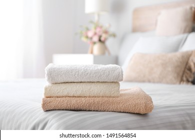 Stack of clean towels on bed