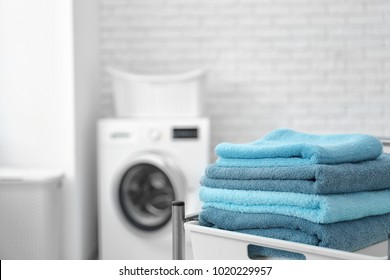 Stack of clean towels on cart in laundromat