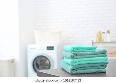 Stack of clean towels on table in laundromat