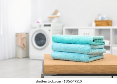 Stack of clean towels on table in bathroom.  Space for text