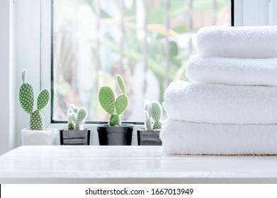 Stapel von sauberen Handtüchern auf weißem Holztisch mit grünem Kakteen-Hintergrund auf Fenstersill im modernen weißen Raum. Kopiert Platz.