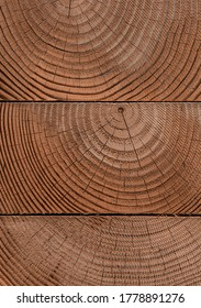 Stack of cleanly cut wooden beams shot straight on showing the woodgrain and tree rings.