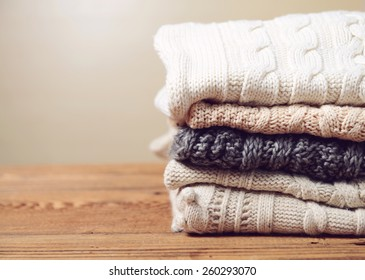 stack of clothes from knitted knitwear on a wooden background, toned image