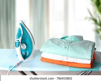 Stack clothes on ironing board and iron.Household domestic work concept.
