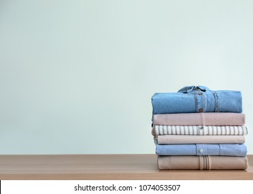 Stack of clothes on table against light background