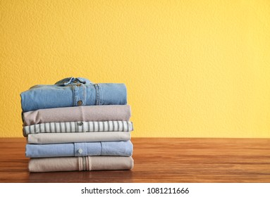 Stack of clothes on table against color background