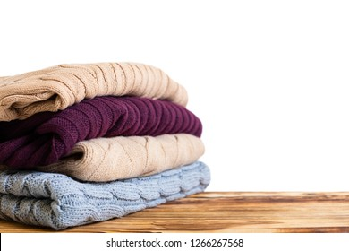 Stack of clothes on table indoor. Household concept. Fresh folded cotton clothing. colored woolen clothing. folded sweater - Image