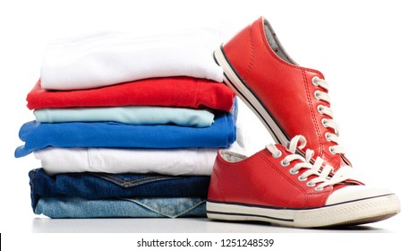 Stack of clothes and red sneakers on a white background. Isolation
