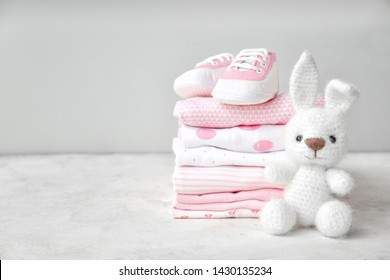 Stack of clothes, shoes and toy on table - Shutterstock ID 1430135234