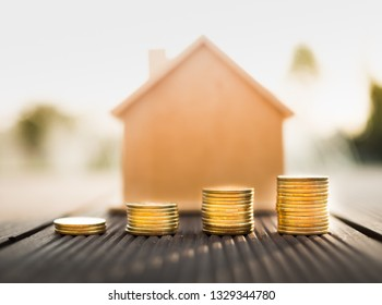 A stack of coin with the house behind, loan for home concept.